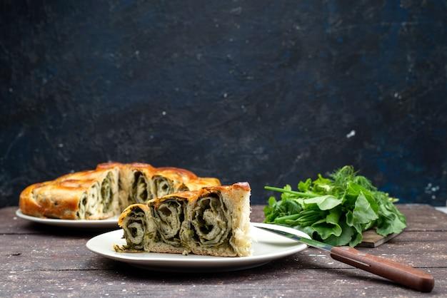 Вид спереди на приготовленную зеленью выпечку внутри тарелки со свежей зеленью на темной поверхности