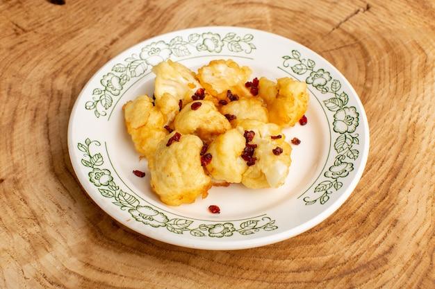 크림 나무 책상에 접시 안에 요리 슬라이스 콜리 플라워의 전면보기