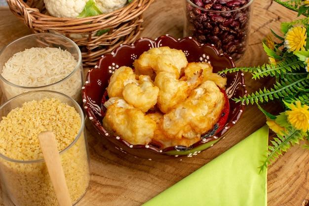 크림 나무 책상에 채소와 생 쌀과 함께 접시 안에 요리 썰어 콜리 플라워의 전면보기