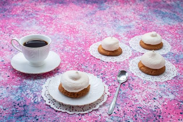 着色された表面上のコーヒーのカップと一緒にクリームとクッキーの正面図