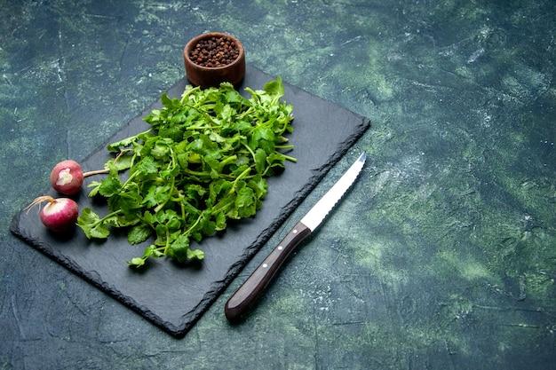 木製のまな板にコリアンダーバンドル新鮮な大根コショウの正面図と空きスペースのある緑と黒の混合色の背景の右側にナイフ