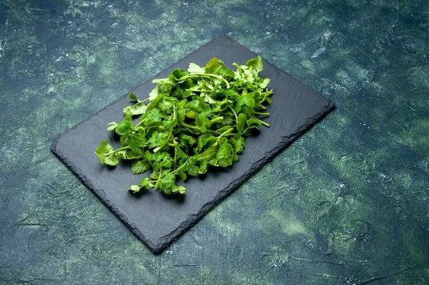 自由空間と緑黒の混合色の背景に木製まな板のコリアンダーバンドルの正面図