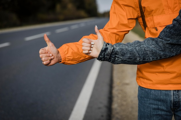 도로 여행을하는 동안 히치 하이킹을하는 부부의 전면보기
