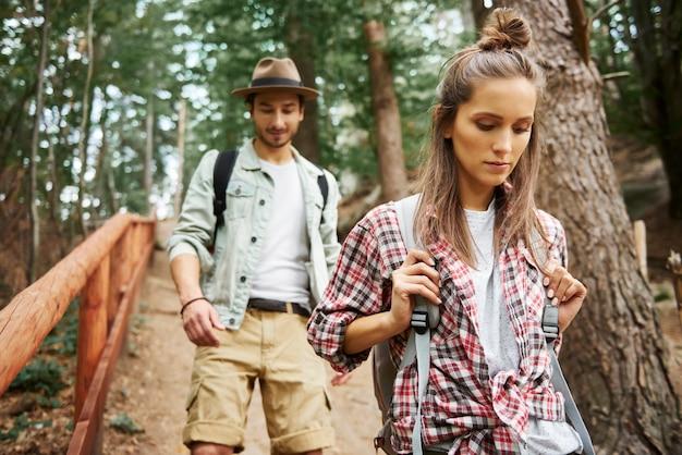 森の中を歩くバックパックとカップルの正面図