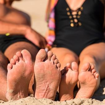 ビーチの砂の上に足を持つカップルの正面図