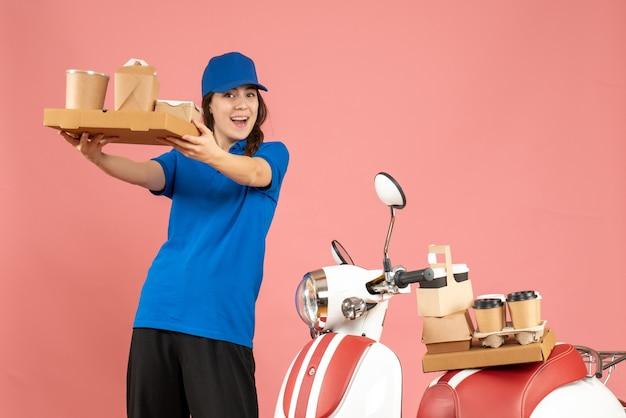 パステル ピーチ色の背景にコーヒーと小さなケーキを示すオートバイの隣に立っている宅配便の女の子の正面図