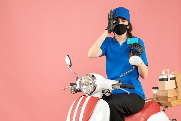 파스텔 복숭아 배경에 안경 제스처를 만드는 주문을 제공하는 은행 카드를 들고 스쿠터에 앉아 의료 마스크와 장갑을 착용하는 택배 소녀의 전면보기
