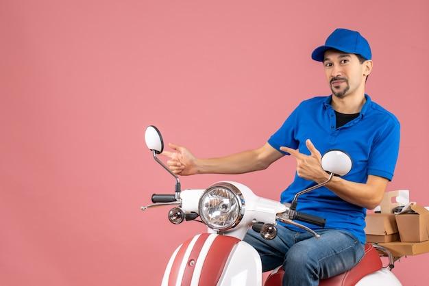 Вид спереди курьера в шляпе, сидящего на скутере, указывая что-то справа на пастельном персиковом фоне