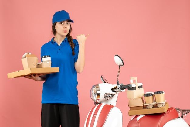 Вид спереди курьерской дамы, стоящей рядом с мотоциклом, держащей кофе и маленькие пирожные, указывающей назад на фоне пастельного персикового цвета