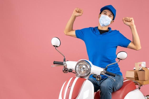 スクーターに座って、パステル調の桃の背景にしかめっ面の帽子をかぶった医療用マスクを着た宅配便の男性の正面図