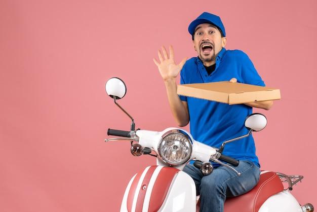 パステル調の桃の背景に驚いた気分でスクーターに座っている帽子をかぶった宅配便の男性の正面図