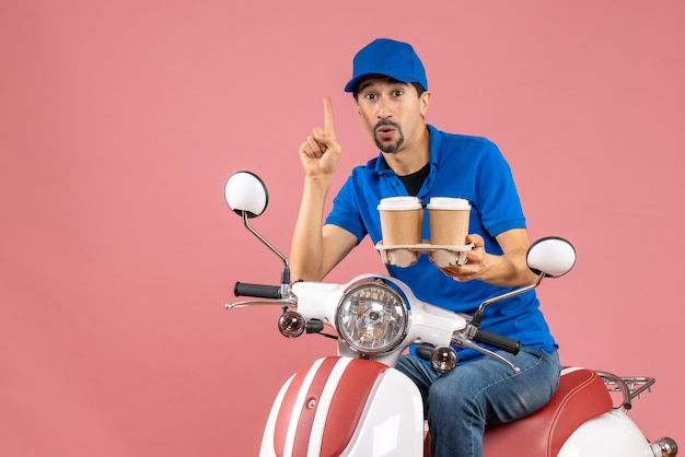 パステル調の桃の背景に上向きのスクーターに座っている帽子をかぶった宅配便の男の正面図