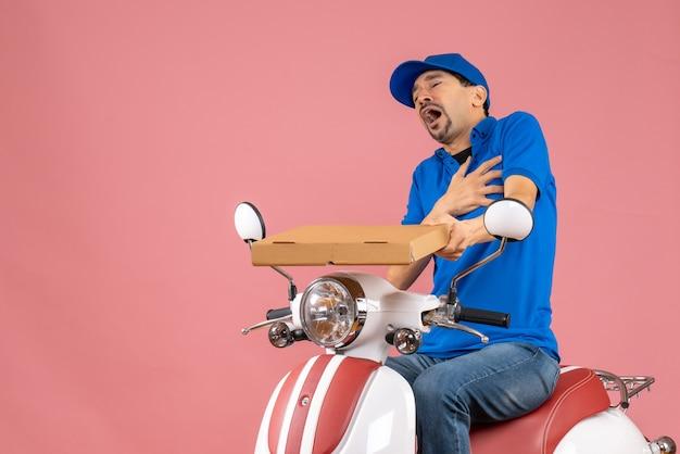 パステル調の桃の背景に心臓発作に苦しんでいるスクーターに座っている帽子をかぶった宅配便の男性の正面図