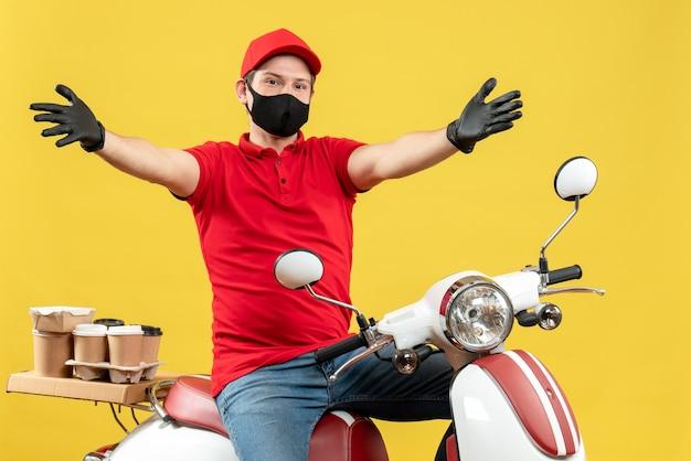 그의 팔을 앞으로 확장 스쿠터에 앉아 주문을 제공하는 의료 마스크에 빨간 블라우스와 모자 장갑을 착용하는 택배 남자의 전면보기