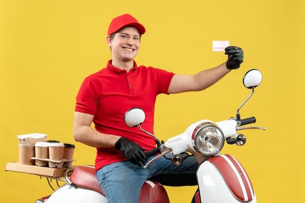 銀行カードを保持しているスクーターに座って注文を配信する医療マスクで赤いブラウスと帽子の手袋を身に着けている宅配便の男の正面図