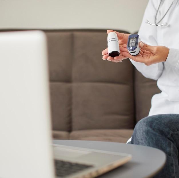 Вид спереди женщины-врача центра восстановления covid, держащей оксиметр и таблетки