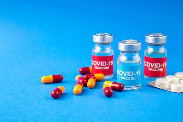 青い波の背景の左側にあるcovid-ワクチンアンプルとカプセルが詰められた錠剤の正面図