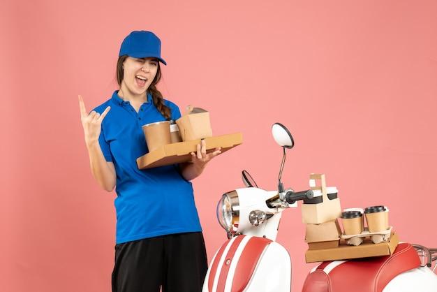 パステル ピーチ色の背景にコーヒーと小さなケーキを保持しているオートバイの隣に立っている狂気の感情的な宅配便の女の子の正面図