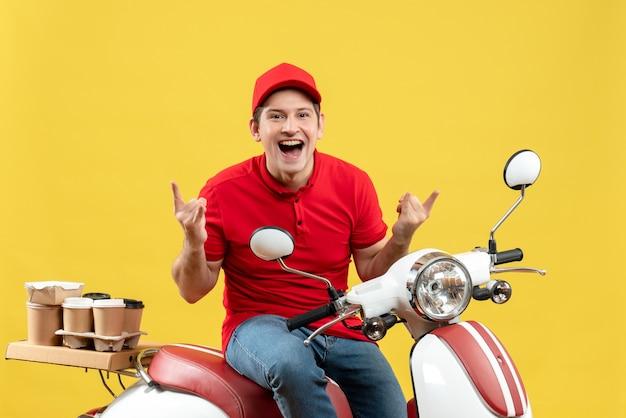 黄色の背景に注文を配信する赤いブラウスと帽子を身に着けているクレイジーな感情的な若い男の正面図