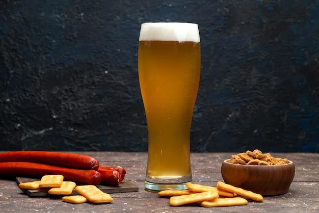 暗い表面にビールと共にクリスプとクラッカーの正面図