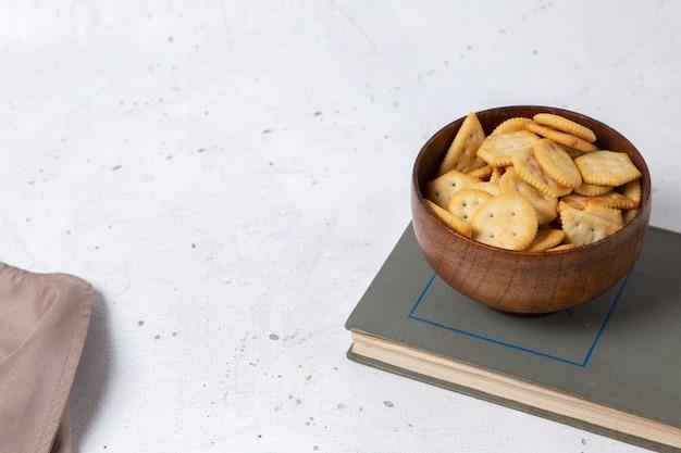 Вид спереди чипсов и крекеров внутри коричневой пластины на светлой поверхности