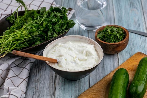 Вид спереди огурцов на доске с йогуртом и зеленью на серой поверхности