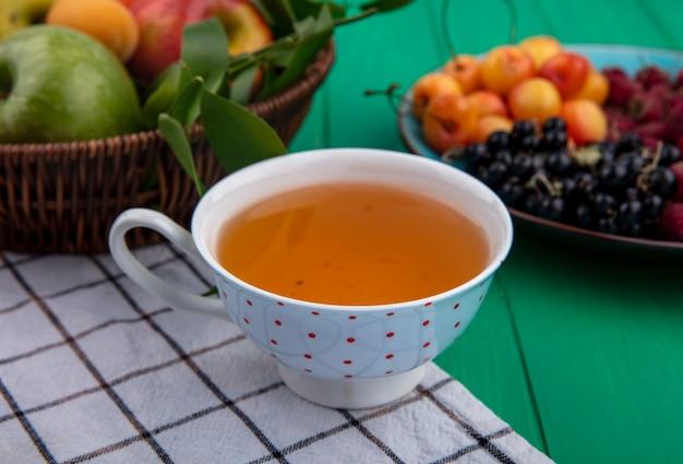 緑の表面にリンゴと白いチェリーとお茶のカップの正面図
