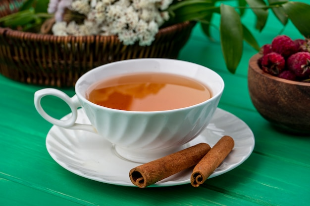 緑の表面にシナモンとラズベリーとお茶のカップの正面図