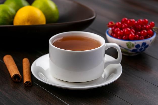 木製の表面にボウルにシナモンと赤スグリとお茶のカップの正面図