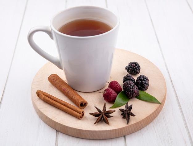 Вид спереди чашки чая с корицей, малиной и ежевикой на подставке на белой поверхности