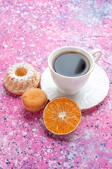 Вид спереди чашки чая с маленьким тортом на розовой поверхности