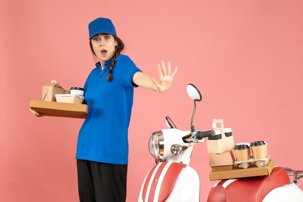 パステル ピーチ色の背景にコーヒーと小さなケーキを保持しているオートバイの隣に立っている好奇心旺盛な宅配便の女の子の正面図