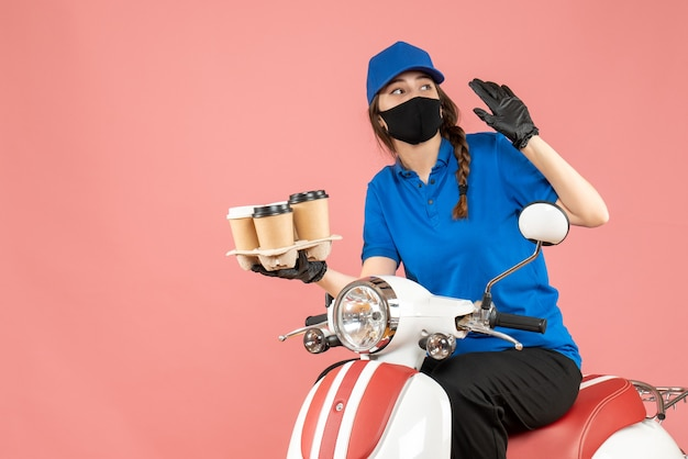 パステル調の桃の背景に注文を保持しているスクーターに座っている医療用マスクと手袋を着た好奇心旺盛な女性配達員の正面図