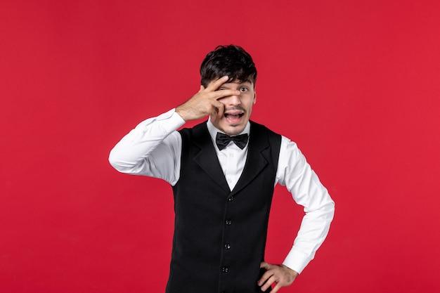 赤い壁に指で顔の半分を閉じる首に蝶と制服を着た好奇心旺盛な男性ウェイターの正面図
