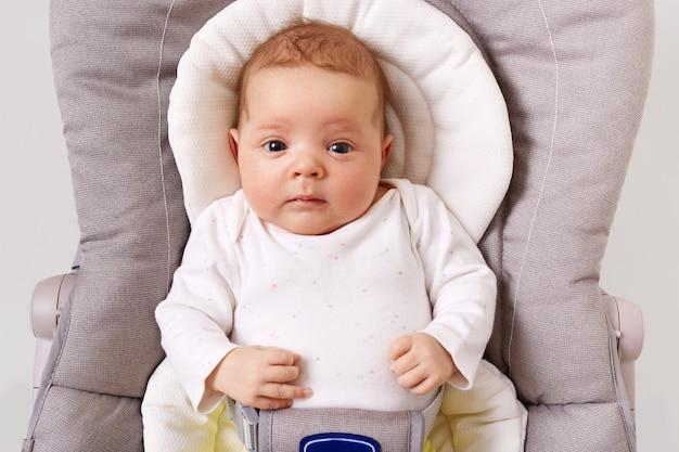 子供の用心棒の椅子に横たわっている白いポディスーツを着ている好奇心旺盛な生まれたばかりの赤ちゃんの正面図