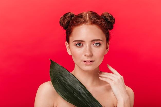 緑の葉を保持し、カメラを見ている好奇心旺盛な裸の女の子の正面図。赤い背景に分離された植物と官能的な生姜の女性のスタジオショット。