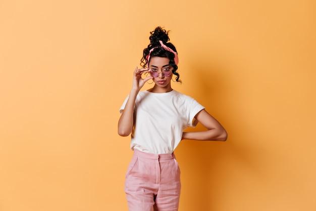 Вид спереди любопытной женщины в модных солнцезащитных очках