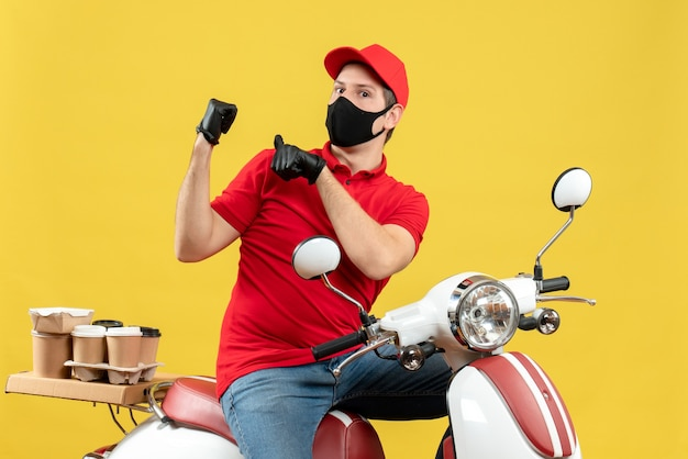 黄色の背景に戻ってスクーターに座って注文を配信医療マスクで赤いブラウスと帽子の手袋を身に着けている好奇心旺盛な若い大人の正面図