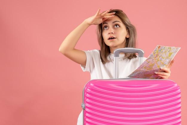 何かを見ている地図を保持しているピンクのスーツケースを持つ好奇心旺盛な少女の正面図