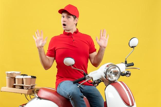 黄色の背景に注文を配信する赤いブラウスと帽子を身に着けている好奇心旺盛な若い男の正面図