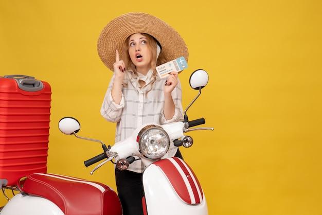 オートバイに座って、上向きのチケットを示す彼女の荷物を収集する帽子をかぶって好奇心旺盛な若い女性の正面図