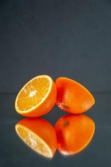 Вид спереди нарезанных свежих апельсинов, стоящих бок о бок на свету на черном фоне со свободным пространством