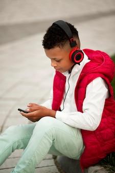 音楽を聞いているかわいい男の子の正面図
