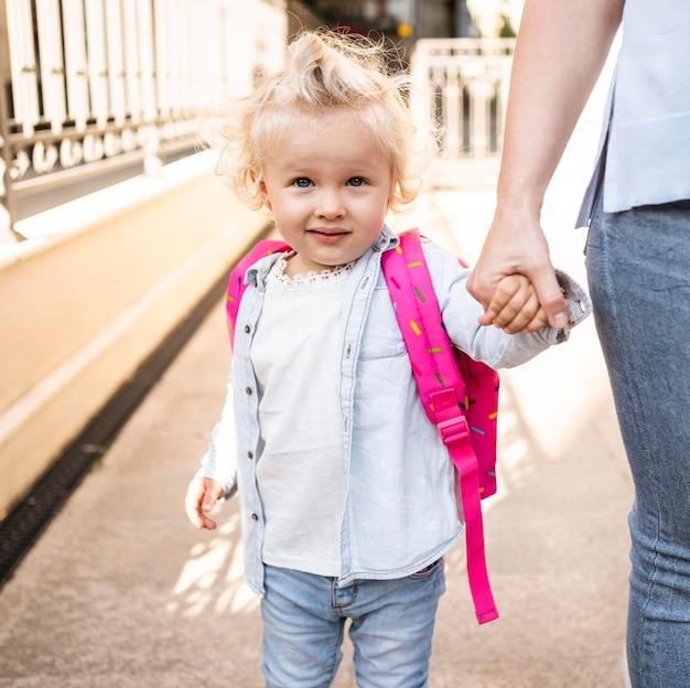 Вид спереди милый ребенок, держащий руку матери на открытом воздухе