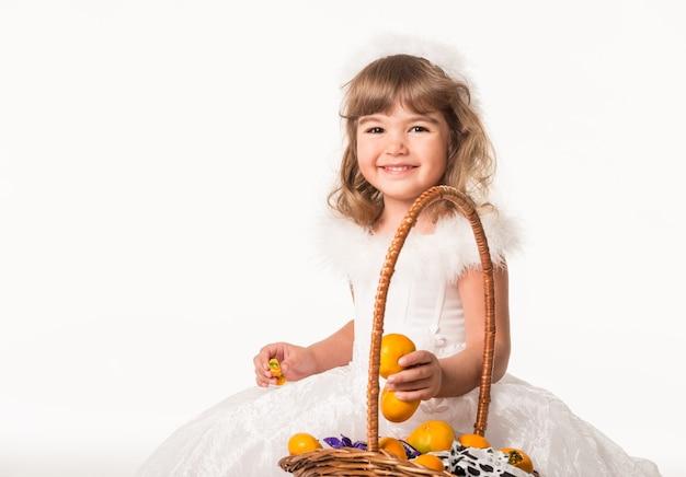 かごの横に立って、柑橘系の果物を保持しているかわいい子の正面図。