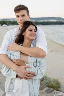 屋外ながら抱きしめるかわいいカップルの正面図