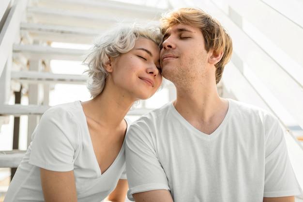 Вид спереди милая пара, прислонившись друг к другу на открытом воздухе