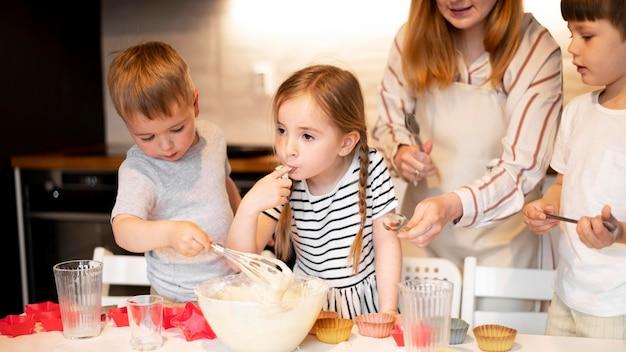 Вид спереди милой семьи готовить вместе