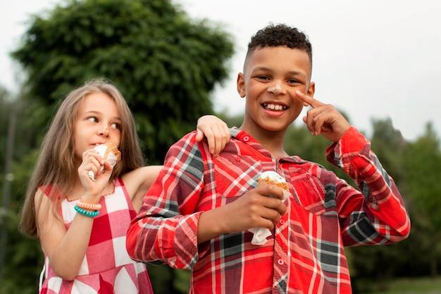 アイスクリームを食べるかわいい友達の正面図
