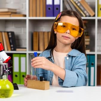안전 안경 및 테스트 튜브와 함께 귀여운 소녀의 전면보기